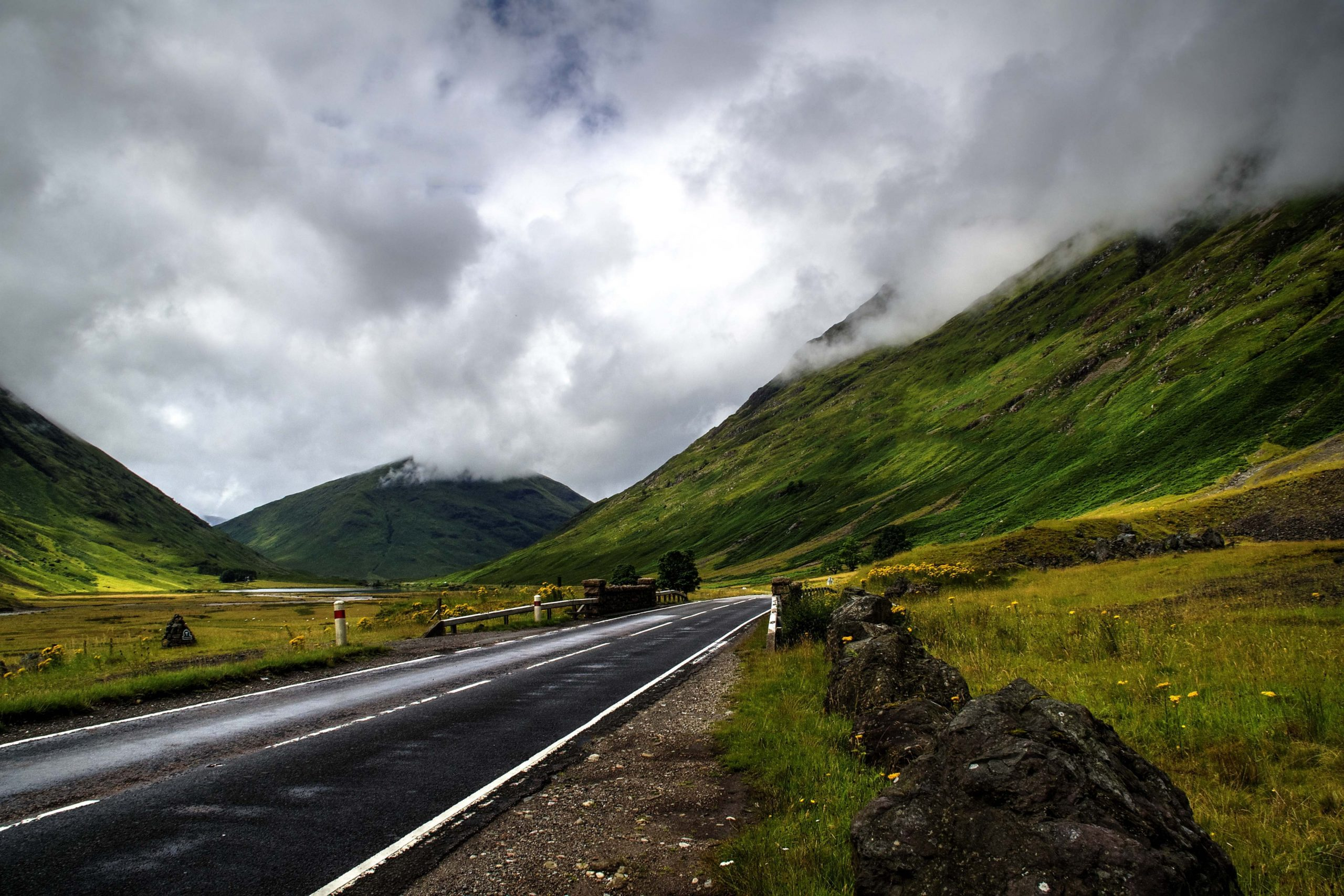 A beautiful shot of the road surrounded by mountains under the cloudy sky